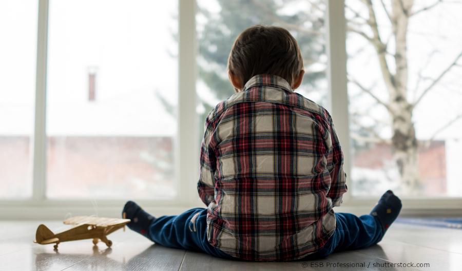 Kleiner Junge neben Spielzeugflugzeug,kehrt den Rücken zu, vor Fenster sitzend