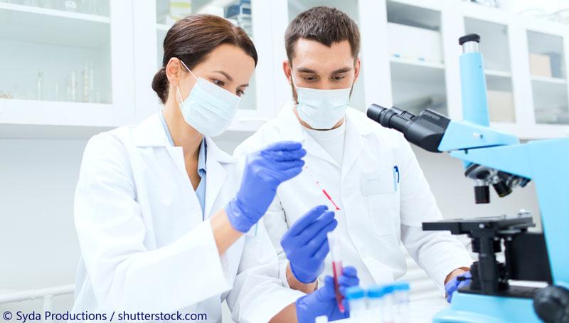 Forscherin und Forscher vor Mikroskop mit Mundschutz, in weißen Laborarbeitskitteln, mit Blutprobe